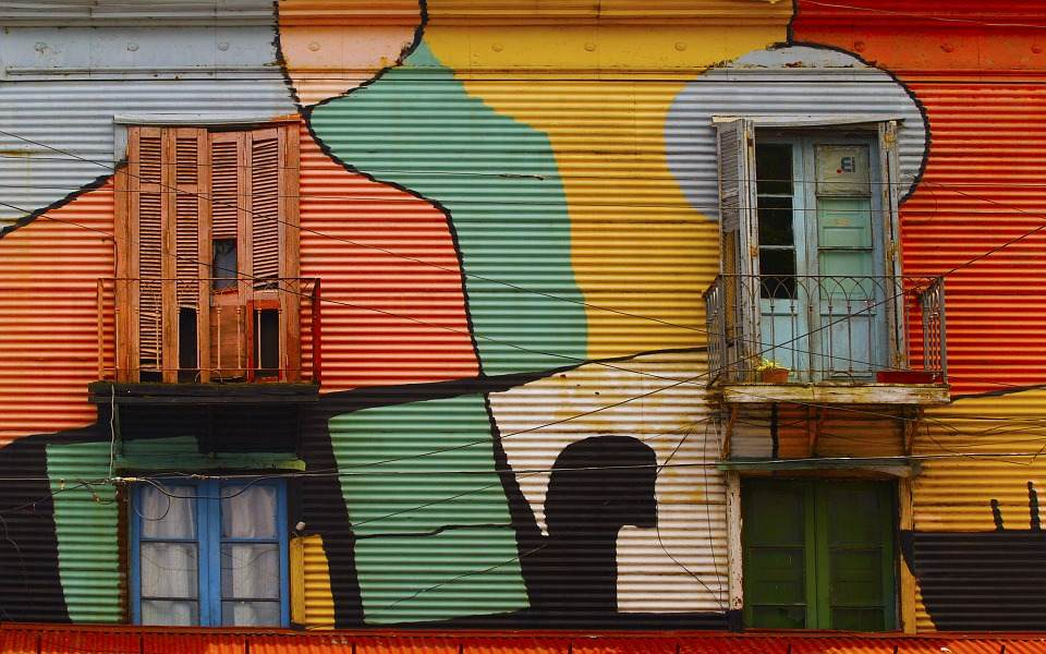 This photo shows some colorful old buildings in Buenos Aires, Argentina. Old wooden windos and small balconies.