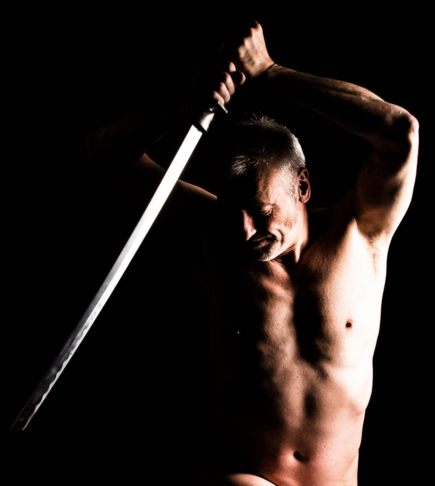 life model Julian, posing with a sword in dramatic light for an artist to draw or sculpt