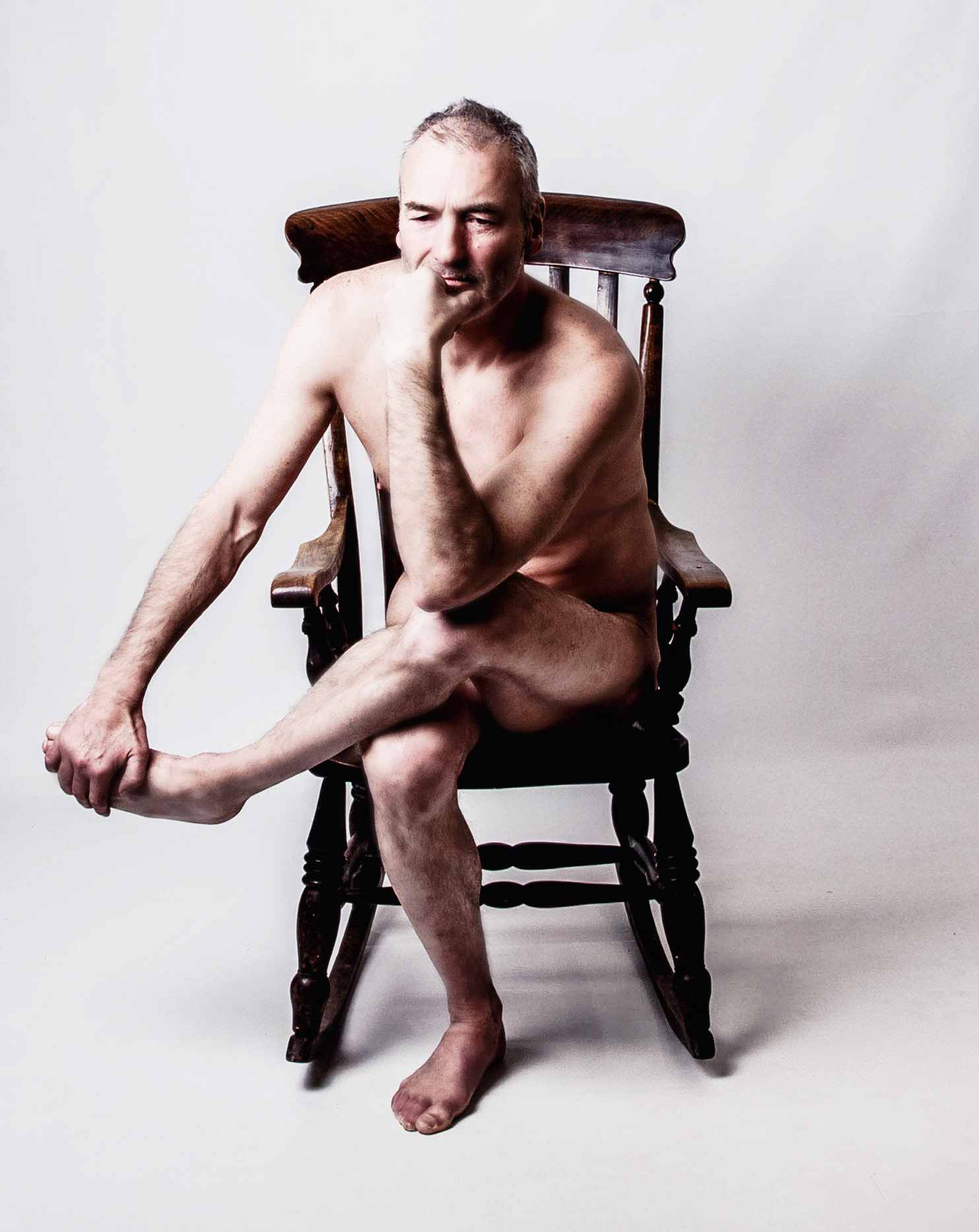 life model Julian, sat on a wooden chair for an artist to draw or sculpt