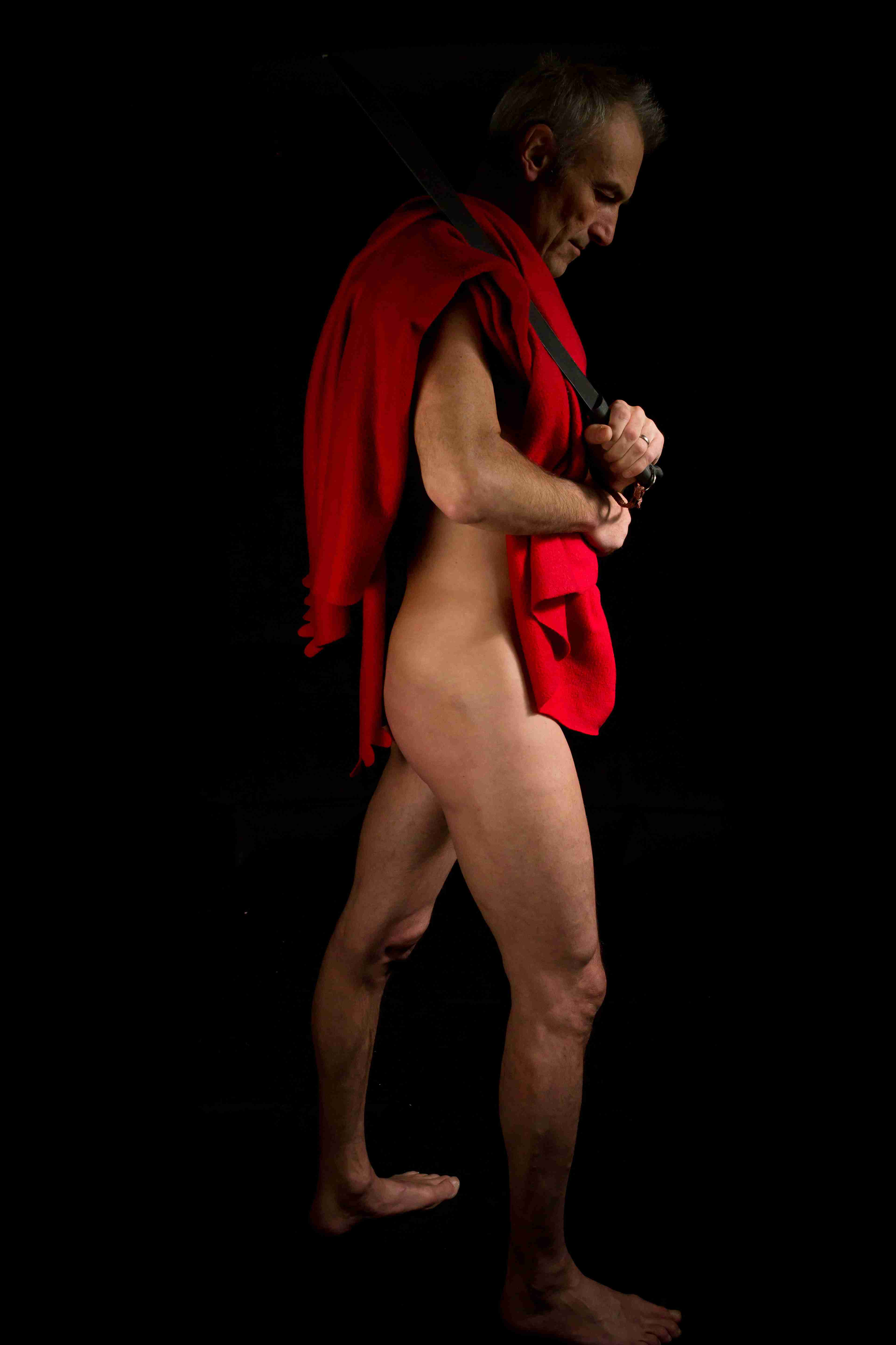 life model Julian, carrying a red coat and black belt for an artist to draw or sculpt