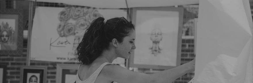 A woman looks at art at an art fair